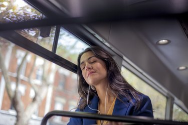 Young woman listening music on a bus with earphones, eyes closed
