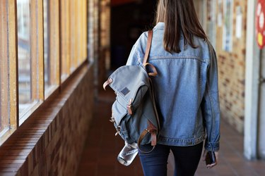 Young woman with backpack walking in corridor
