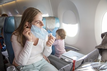 concept trip with a child to Asia, fear of coronavirus covid-19. young beautiful mother in an airplane chair puts on a medical respiratory mask. a cute baby is sitting next to her