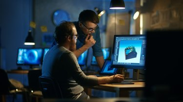 Two Male Game Developers Discuss Game Level Drawing, One Uses Graphic Tablet. They Work Late at Night in a Loft Office.