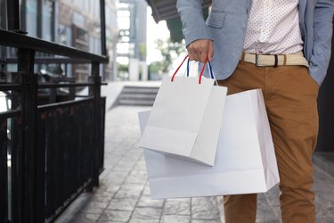 What States Have No Sales Tax on Clothing?Shopaholic man walking on commercial street with shopping bags