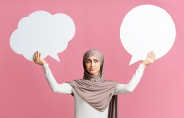 Two empty speech bubbles in hands of concerned muslim woman