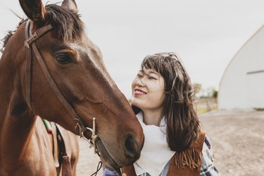 cute chinese cowgirl taking care of horse