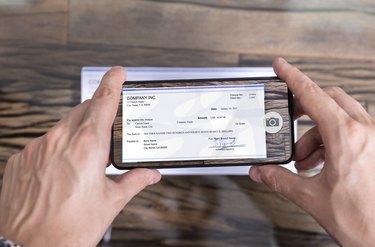 Man Taking Photo Of Cheque To Make Remote Deposit