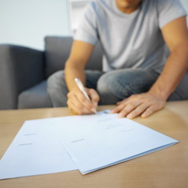 How Can I Get a Free Preliminary Title Report?Man signing a deed of sale