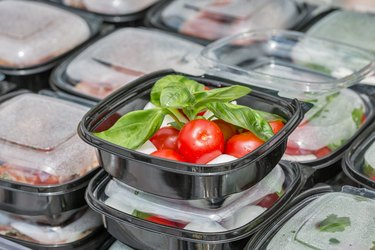 Street food box with mozzarella cheese, cherry tomatoes and basil.