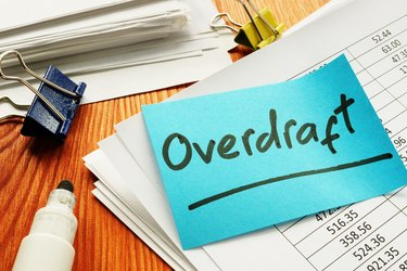 Overdraft sign and stack of accounting documents.