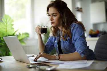Young woman drinking coffee and working at home