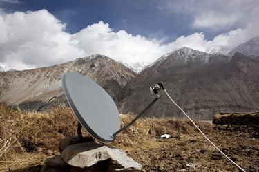 Satellite tv dish in front of snowy mountains