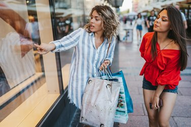 Two young cheerful female friends shopping in the city