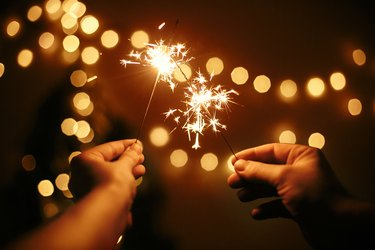 Glowing sparklers in hands on background of golden christmas tree lights, couple celebrating in dark festive room. Happy New Year. Space for text. Fireworks burning in hands. Happy Holidays