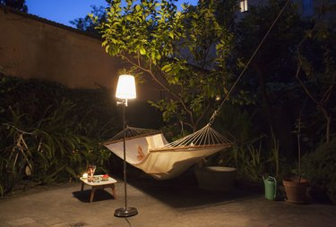 Woman reading in the hammock in garden at night