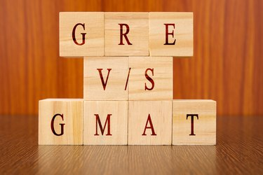 Concept of GRE vs GMAT Exam differences in wooden block letters on table.