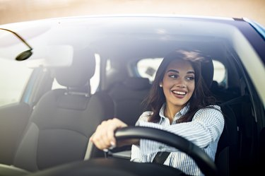 Cute young success happy brunette woman is driving a car.