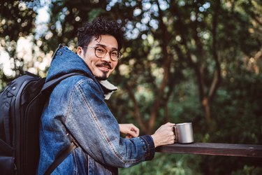 Young asian man with reusable coffee cup smiling joyfully at camera in country park
