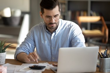 Focuses man calculate expenses pay bills online