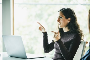 Businesswoman explaining project details to colleagues during meeting in office conference room