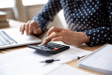 Close up Indian woman planning budget, using calculator and laptop