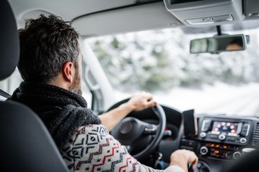 Rear view of mature man driving car on snowy road.