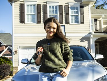 Portrait of teenage girl with her first car