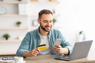 Happy Caucasian man buying things online, using smartphone, laptop and credit card, enjoying shopping in internet