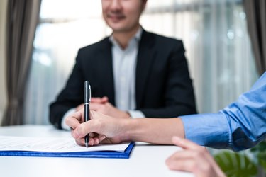 Close up hands of businesswoman sign contract agreement on paper with pen after negotiation for Business deal and acquisition. Investor girl consult with Salesman banker for loan insurance investment.