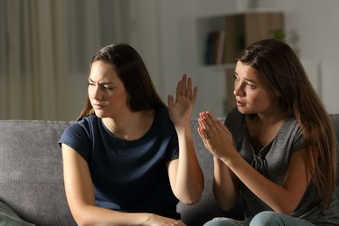 Woman begging forgiveness and friend ignoring her