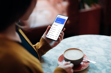 Close-up Shot Of Young Woman Managing Bank Account on Smartphone At Cafe