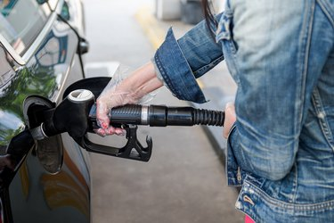 Woman's hand with gloves holding hose from gas pump