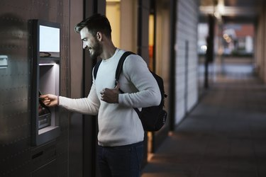 Man withdrawing money at an ATM in the city