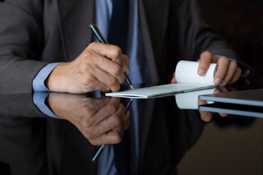 Businessman in suit hand signs cheque. Paycheck concept.