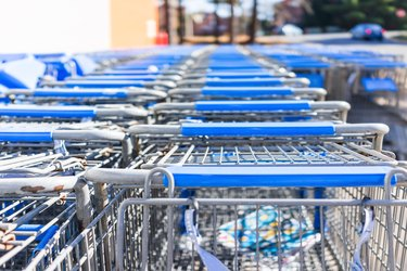 Many rows of blue shopping carts outside by store with closeup by parking lot
