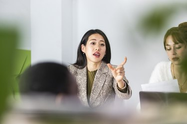 Businesswoman gesturing while talking by colleague at office