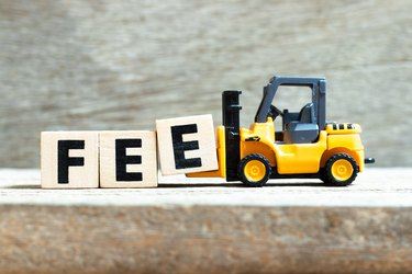 Toy forklift hold letter block e to complete word fee on wood background