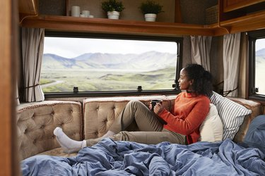 Woman with coffee cup on bed in camper van