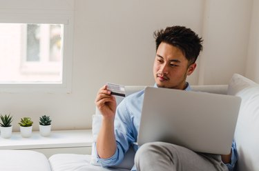 Asian shopping online with credit card and laptop