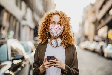 Portrait of a young woman with face mask using mobile phone