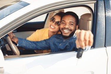 African American Spouses Showing New Car Key Sitting In Automobile