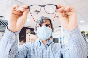 Middle-aged man wearing flu mask holding modern glasses in his hands