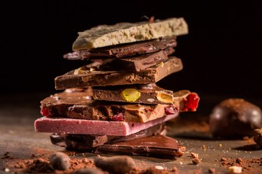 Stack of assorted chocolate with cocoa and cocoa beans