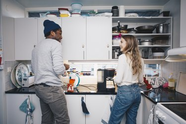 Happy young roommates cooking in kitchen