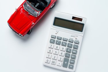 Calculator and sports car isolated on white background