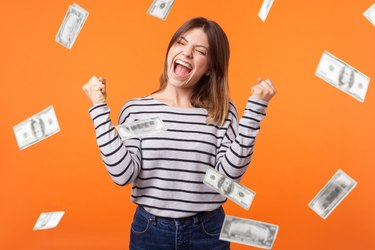 Money rain. Yes I did it! Portrait of joyous winner, young woman in casual shirt standing with clenched fists and closed eyes, celebrating victory and richness.