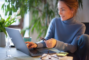 Woman checking computer with credit card in hand