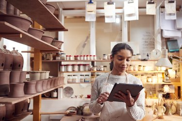 Female Potter In Ceramics Studio Checking Orders Using Digital Tablet