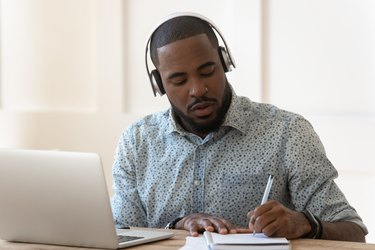 African student wearing headphones listens audio course makes notes