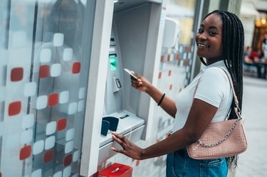 African american woman using credit card and withdrawing money from an ATM