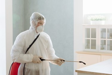 A professional contractor pests pests or viruses by disinfecting a home. coronavirus epidemic covid-19.