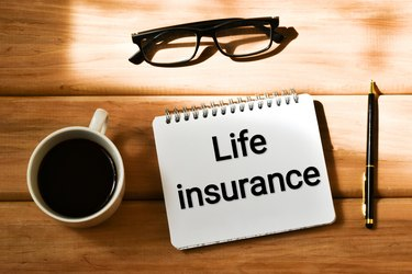 LIFE INSURANCE text written in a notepad near a cup coffee, eyeglasses and pen on a wooden background. Business concept. Flat lay.