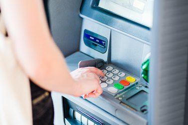 Person entering PIN code using ATM bank machine to withdraw money. Close-up.